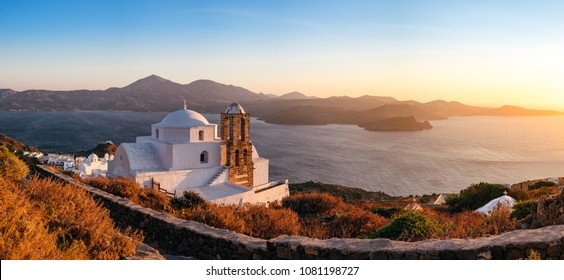 Panoramic view of traditional Greek church, village and ocean coast, Plaka village on Milos island, Greece