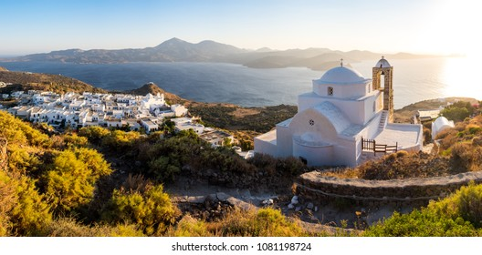 Panoramic view of traditional Greek village Plaka and white church at sunset, Milos island, Greece