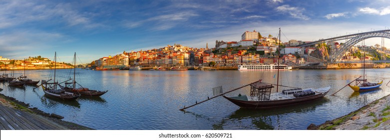 Panoramic view of traditional rabelo boats with barrels of Port wine on the Douro river, Ribeira and Dom Luis I or Luiz I iron bridge on the background, Porto, Portugal.