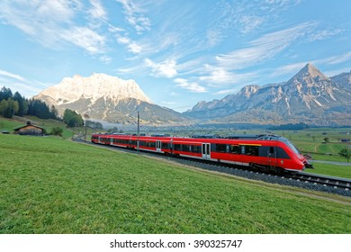 Panoramic view of a train traveling on green fields with Mountain Zugspitze in background on a beautiful sunny day in Lermoos, Tirol, Austria ~ Beautiful summer scenery of idyllic Tyrolean countryside
