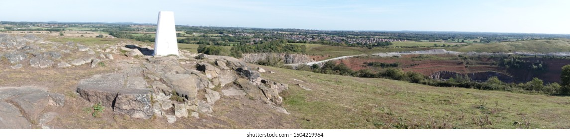 A panoramic view of a trigonometry point on top of granite rocks with a large granite quarry to the right of picture and a village in the background.