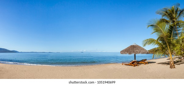 Panoramic view of two loungers under a straw parasol on a beautiful tropical beach