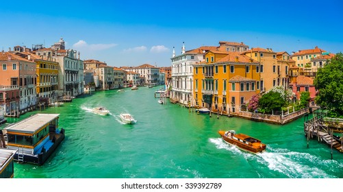 Panoramic view of typical Canal Grande scene with colorful houses and busy boats and gondolas on a  sunny day in Venice, Italy