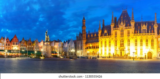 Panoramic view of typical Flemish colored houses and statue of Jan Breydel and Pieter de Coninck on the Grote Markt or Market Square during evening blue hour, Bruges, Belgium