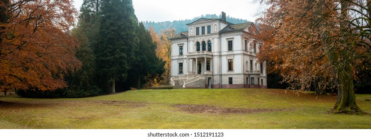 A panoramic view of a typical huge film mansion and its garden, autumnal aesthetic. The location is the Black Forest region, in Germany.