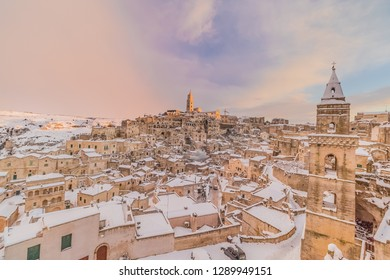 panoramic view of typical stones Sassi di Matera and church of Matera 2019 under blue sky with clouds and snow on the house,travel and christmas holiday on snowflakes at sunset,capital of europe cultu