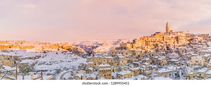 panoramic view of typical stones Sassi di Matera and church of Matera 2019 under blue sky with clouds and snow on the house,  travel and christmas holiday on snowflakes at sunset,capital of culture