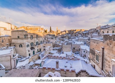 panoramic view of typical stones Sassi di Matera and church of Matera 2019 under blue sky with clouds and snow on the house, travel and christmas holiday on snowflakes,capital of europe culture 2019