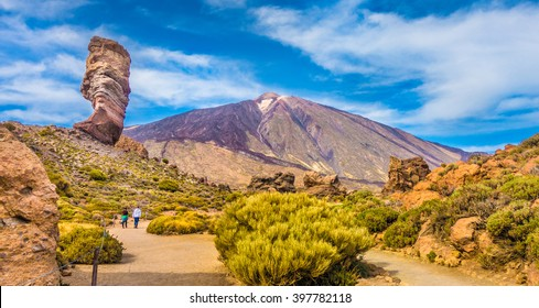 Panoramic view of unique Roque Cinchado unique rock formation with famous Pico del Teide mountain volcano summit in the background on a sunny day, Teide National Park, Tenerife, Canary Islands, Spain