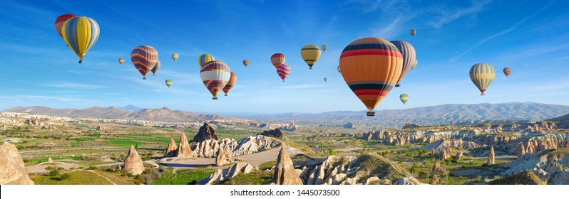 Panoramic view of unusual rocky landscape in Cappadocia, Turkey. Colorful hot air balloons fly in sky over deep canyons, valleys and fairy chimneys of Cappadocia region.