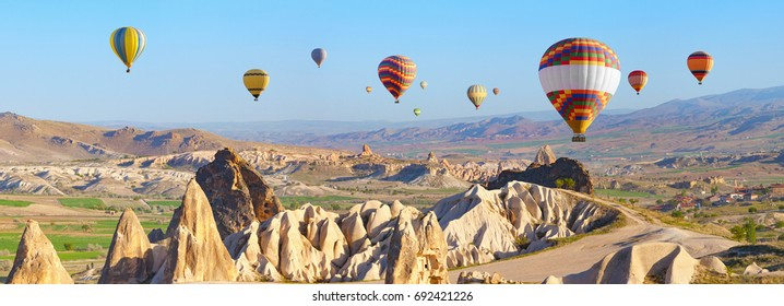 Panoramic view of unusual rocky landscape in Cappadocia, Turkey. Hot air ballooning in morning is most amazing attraction in Kapadokya.