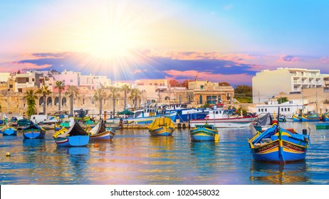 Panoramic view of Valletta harbour in Malta, with boats and architecture illuminated by sunset light
