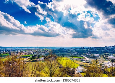 Panoramic view of the valley of the Italian city of Locorotondo, with clouds and trullis in the background.