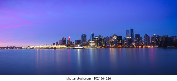 Panoramic view of Vancouver Skyline at Sunrise with City Lights as seen from Stanley Park, Vancouver, British Columbia, Canada