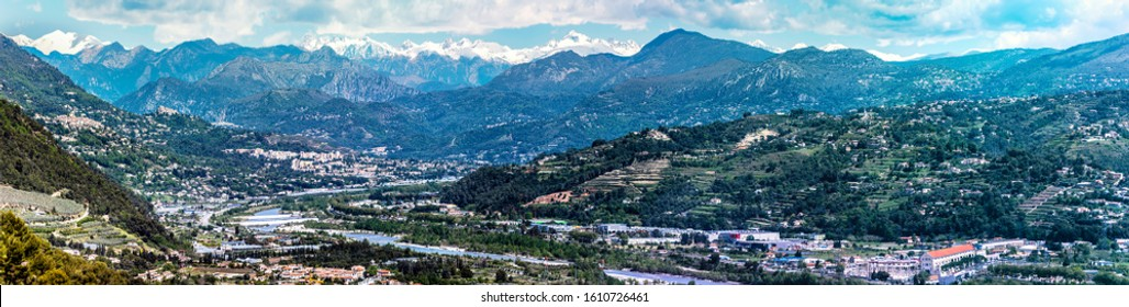Panoramic view of Var Valley from Saint Laurent du Var village, the suburb of Nice city. Mountains of Mercantour National Park isa at background. French Riviera.