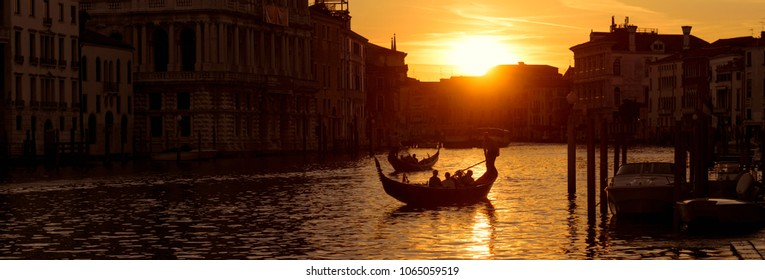Panoramic view of Venice at sunset, Italy. Horizontal banner of night Venice for website header. Gondolas with tourists sail on the Grand Canal in Venice. Romantic water trip in Venice at dusk.