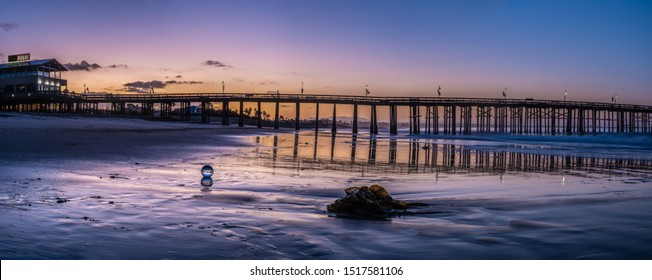 Panoramic view of Ventura Pier reflected in wet sand of beach in early Autumn at low tide.