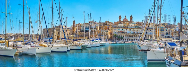 Panoramic view of Vittoriosa marina with luxury sail yachts and hilly Senglea city on the background, Birgu, Malta.