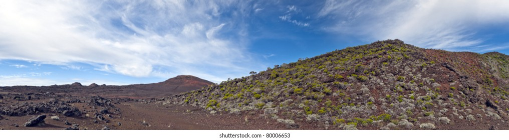 Panoramic view of volcanic landscape of Reunion Islands with blue sky and cloudscape background.