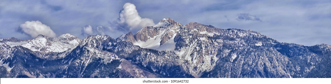 Panoramic view of Wasatch Front Rocky Mountain, highlighting Lone Peak and Thunder Mountain from the Great Salt Lake Valley in early spring with melting snow, pine trees, scrub oak and quaking aspen