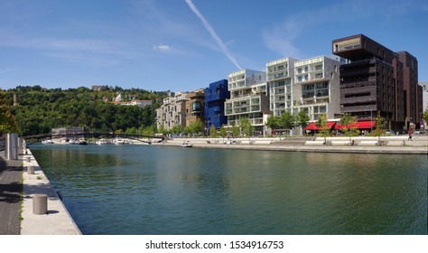 Panoramic view at water channel with parking for boats, pedestrian bridge and modern architecture, The Confluence District in Lyon, France