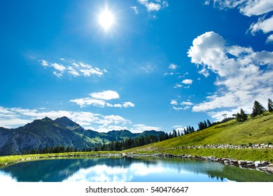 Panoramic View of a water mirror lake in alpine mountains of Nassfeld. Beautiful blue sky with clouds at the background. Hermagor, Carinthia.