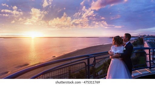 Panoramic view to a wedding couple standing on the roof and watching the sunset