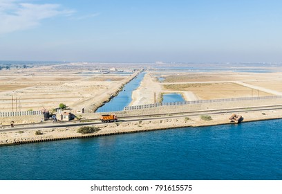 Panoramic view of the western side of the Suez Canal, railway, truck, water canals among sand dunes. View from the water