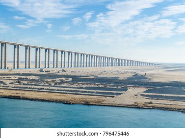Panoramic view of the western side of the Suez Canal, with  part of Suez Canal Bridge, going off into the distance to the horizon line. View from the water, Suez Canal, Egypt