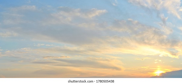 A panoramic view of white cirrus clouds against a blue sky background, illuminated by the setting sun.