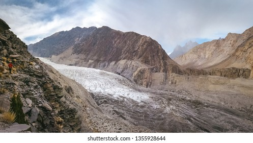 Panoramic view of white Passu glacier and glacial moraine, surrounded by mountains in Karakoram range. Gojal Hunza. Gilgit Baltistan, Pakistan.
