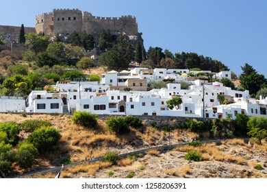 panoramic view of the white village of Lindos at rhodes with the historic acropolis at the mountain top in the background