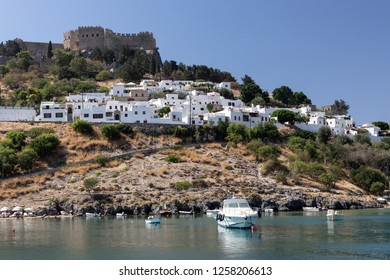 panoramic view of the white village Lindos with a boat swimming  in the St. Pauls' Bay in the foreground