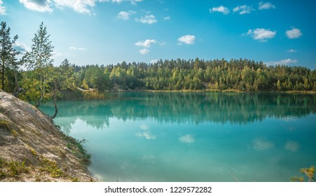Panoramic view of a wild blue lake with azure water in a chalky quarry surrounded by forest