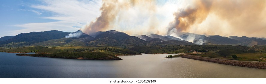 Panoramic view of a wildfire burning through the dry forests and threatening houses and buildings in the mountains