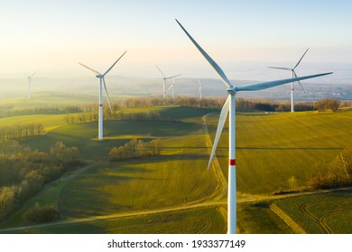 Panoramic view of wind farm or wind park, with high wind turbines for generation electricity with copy space. Green energy concept. - Shutterstock ID 1933377149