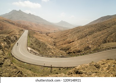 Panoramic view of winding road with cyclists at Astronomical Viewpoint of Sicasumbre, Fuerteventura, Spain.