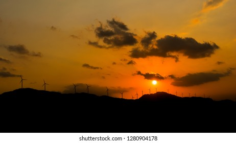 Panoramic view of a windmill farm on the mountains at sunset, Karnataka, India. Silhouette of wind turbines. Sustainable development.