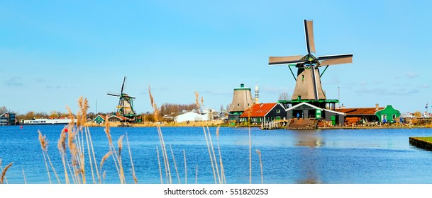 Panoramic view of windmills in Zaanse Schans, traditional village in Holland, reflection in lake, blue sky