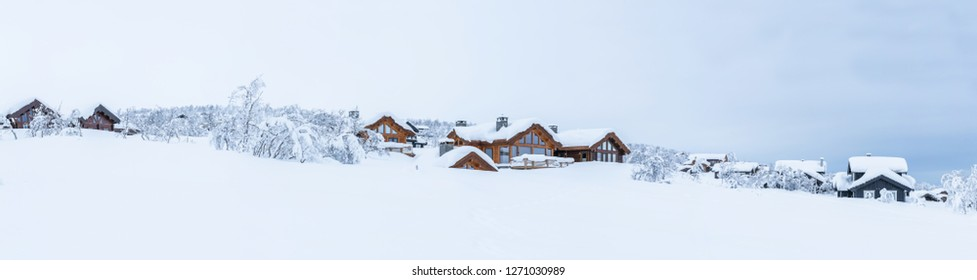 Panoramic view of winter landscape with snow covered trees and wooden cabins in Beitostolen. Winter in Norway