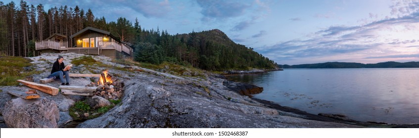 panoramic view woman reading near campfire in norway