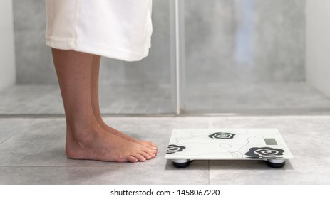 Panoramic view of woman in white and comfort bathrobe standing near weigher in bathroom with copy space