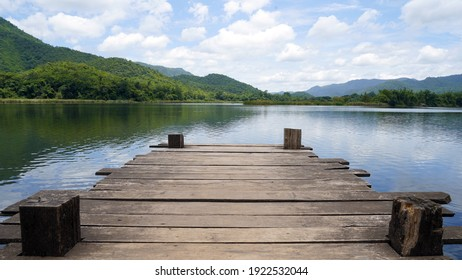 Panoramic view of Wooden bridge lake with Green mountain, bright blue sky and lake at the background with Empty wooden floor. can be used for display product Mock Up. Panoramic Nature Scene.