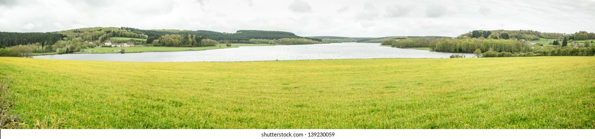 Panoramic view, Yellow flower fields by the Saint Agnan Lake in Burgundy, France