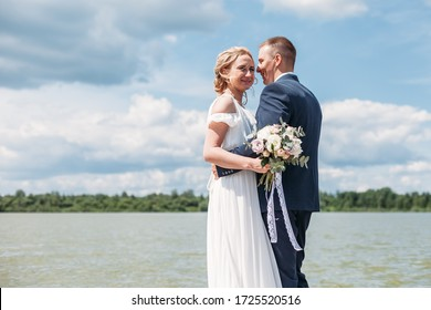 Panoramic view young couple bride in white and groom in blue standing among lake, posing and embracing. Conceptual wedding at nature outdoor in summer season. Wedding, family, love story concept