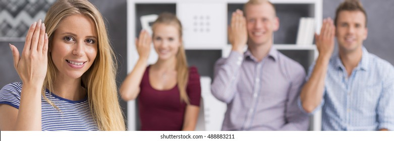 """Panoramic view of a young people showing the word """"to welcome"""" using sign language"""
