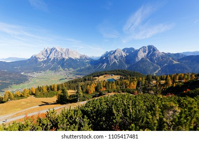Panoramic view of Zugspitze & Sonnenspitze, with colorful autumn trees on mountainside & Ehrwald village in the valley at the foot of rugged mountains under blue sunny sky, in Lermoos, Tirol, Austria