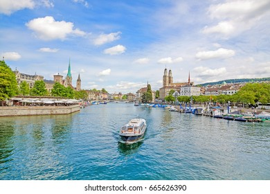 Panoramic view of Zurich city center with famous Minster Grossmunster, and Fraumunster, and St. Peter church. Cruise vessel on river Limmat in front on a sunny day with clouds in summer.