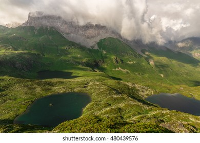 Panoramic views of three mountain lakes in the valley and high cliffs in the clouds