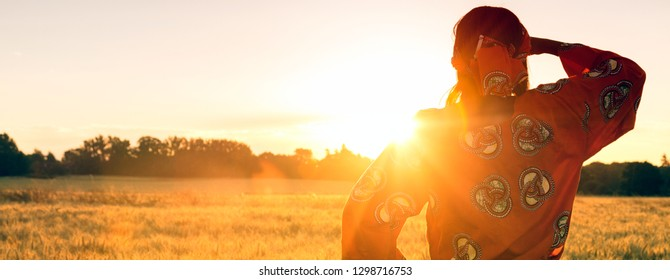 Panoramic web banner African woman in traditional clothes looking across a field of barley or wheat crops at sunset or sunrise